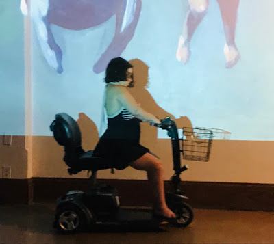 Amber DiPietra, a short disabled woman in an old-fashioned 1950's blue and white bathing suit drives a mobility scooter across a stage. Behind her is a projection of Sunaura Taylor's painting, Self-Portrait with Manatee.