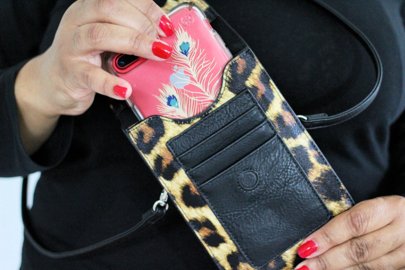 a woman holding a leopard crossbody purse