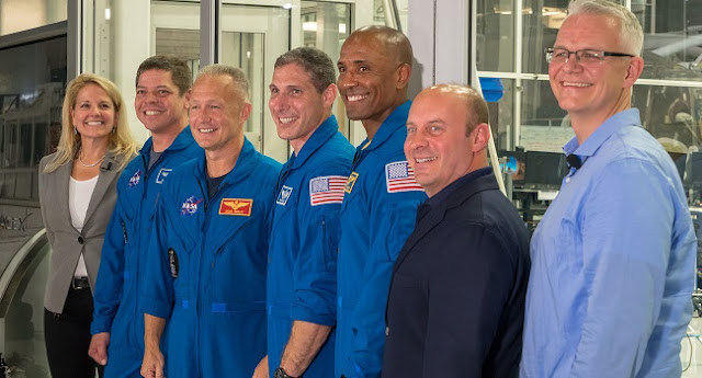 nasa astronauts stand behind spacex s crew dragon spacecraft
