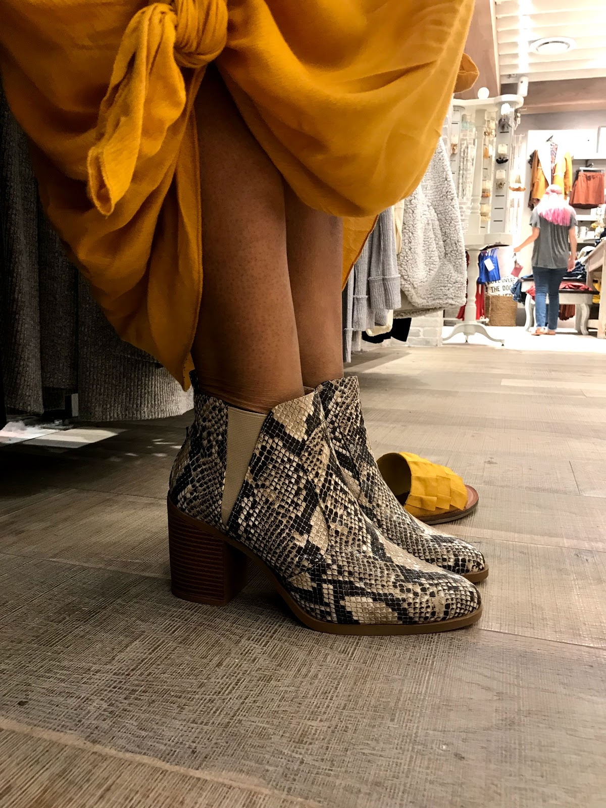 Image: Woman in yellow dress try on leopard black and white booties for Fall. Shopping vlog seen first on Bits and Babbles blog.
