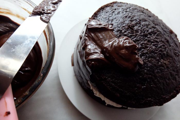 spreading chocolate ganache on cake