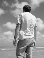 Back view of a man looking towards the sea, in black and white