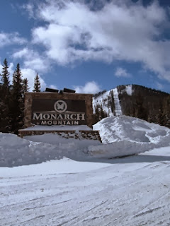 Sun shinning above the Monarch Mountain entrance sign, with the ski area in the distance all covered in snow.