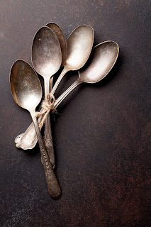 Imagine contains: A bundle of vintage spoons, positioned as if falling one after the other to the side