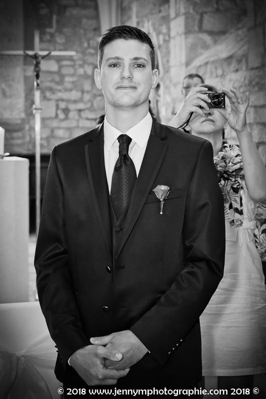 portrait du marié, photo noir et blanc, la marié attend la mariée à l'autel dans l'église