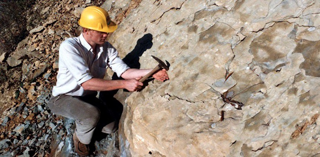 A imagem mostra uma rocha muito grande e algumas pedras caídas do lado, a cor da rocha é marrom esbranquiçada. Na frente da rocha grande há um homem branco, vestindo uma camisa branca, uma calça caqui marrom, um sapato marrom e um capacete amarelo de proteção. O homem segura um martelo que está usando na rocha.