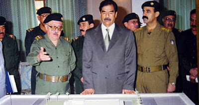 Tariq Aziz (left) and Saddam Hussein (center)