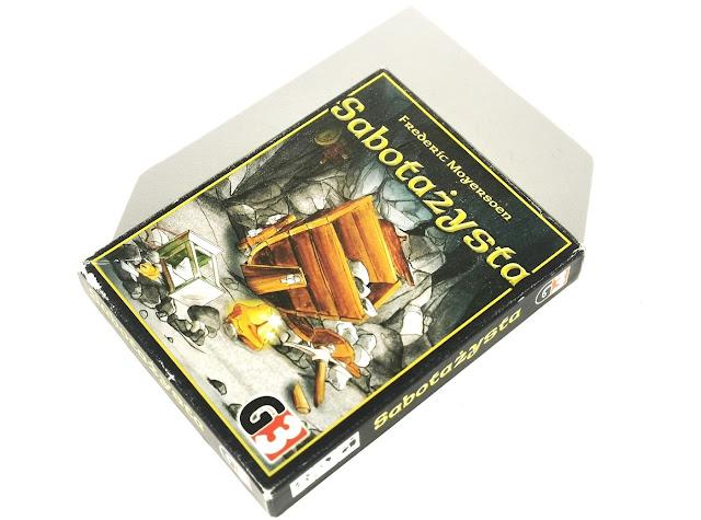 na zdjęciu pudełko gry Sabotażysta z ilustracją potłuczonego wózka górniczego i innych narzędzi oraz bryłki złota