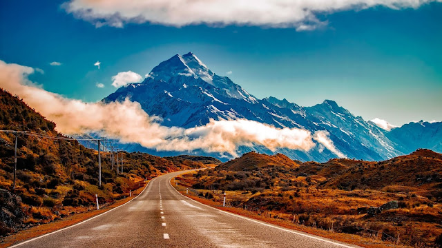 Estrada de mão dupla, faz curva para a direita, com montanhas ao fundo e nuvens no topo.