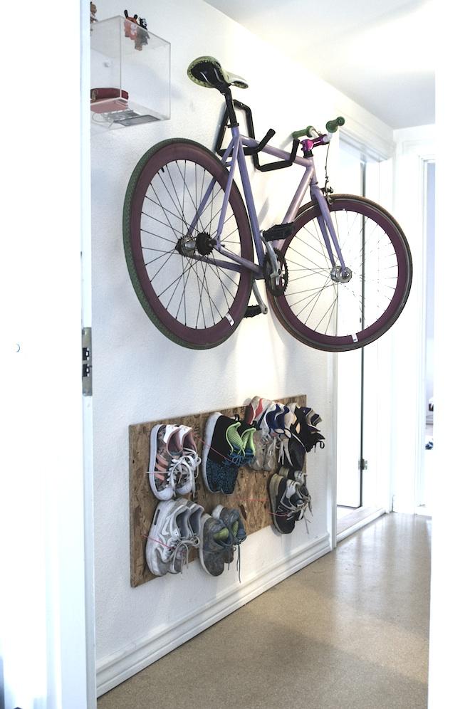 bicicleta colgada en hall y zapatero colgado en la pared con un corcho y cuerdas