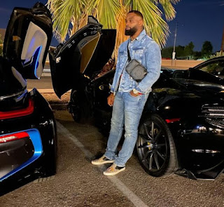 Tyron Woodley posing for picture with a car