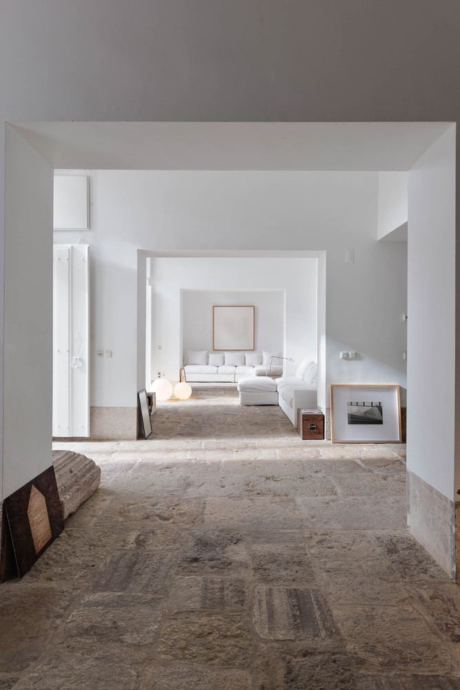 Salón blanco con piedras originales en el suelo