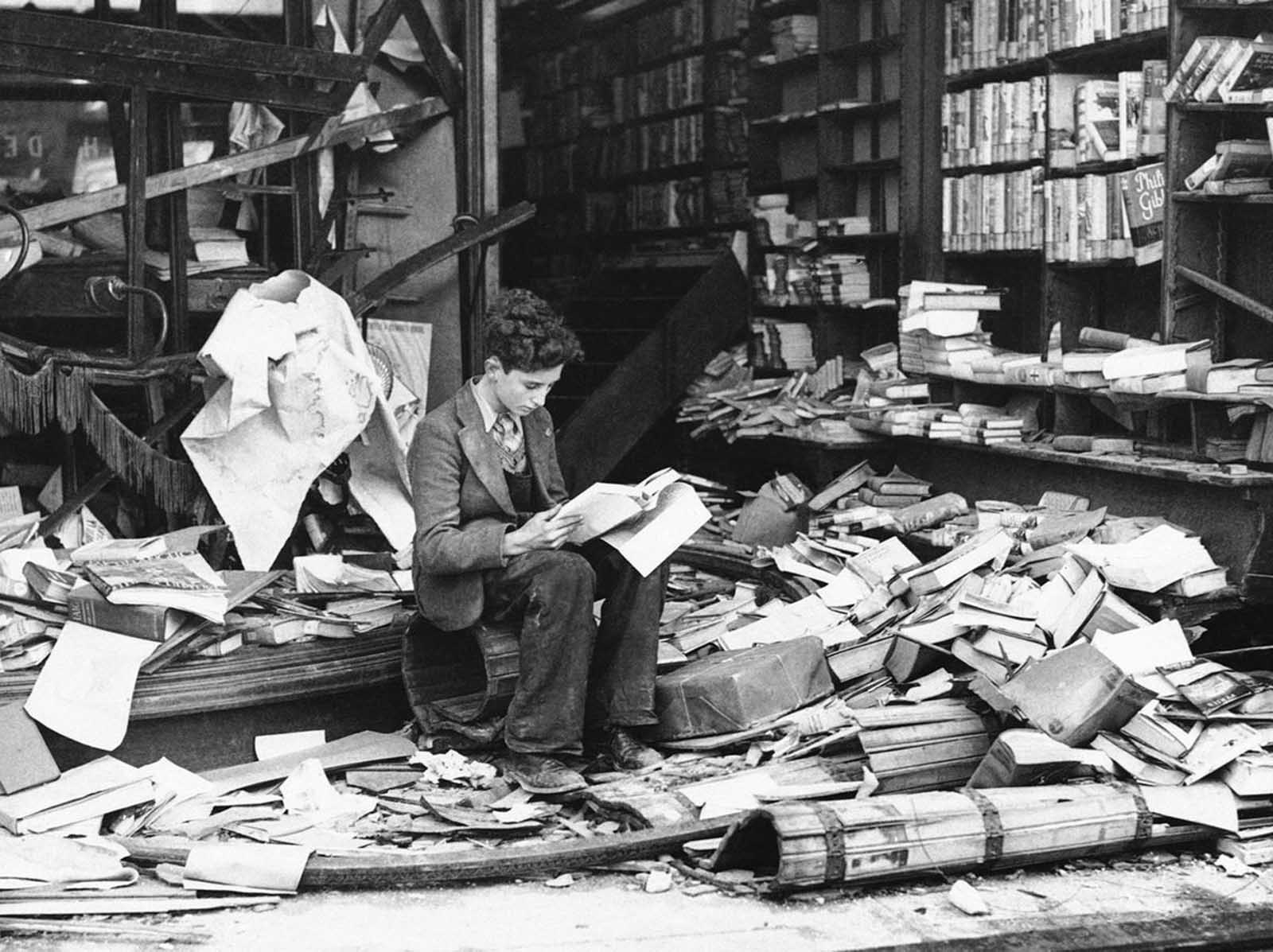 A boy sits amid the ruins of a London bookshop following an air raid on October 8, 1940, reading a book titled