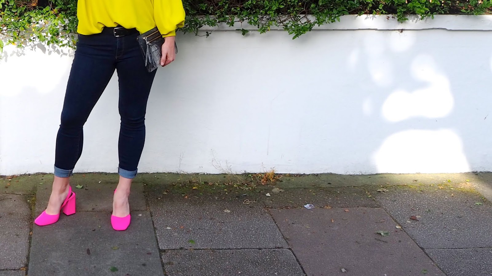 neon pink chunky heels with rolled up dark blue jeans