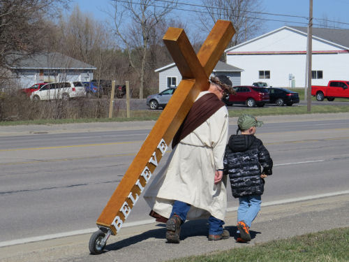 man dressed as Jesus carrying a cross