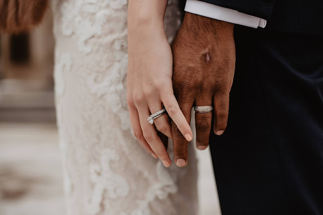 Close up of a bride and groom's hands.