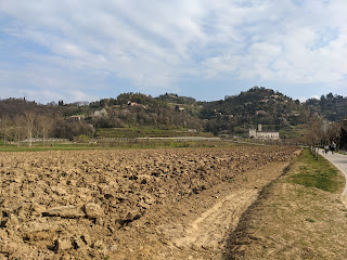 Looking over a tilled field and view toward Monastero d'Astino.
