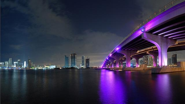 The Miami skyline at night, with a brightly coloured bridge.