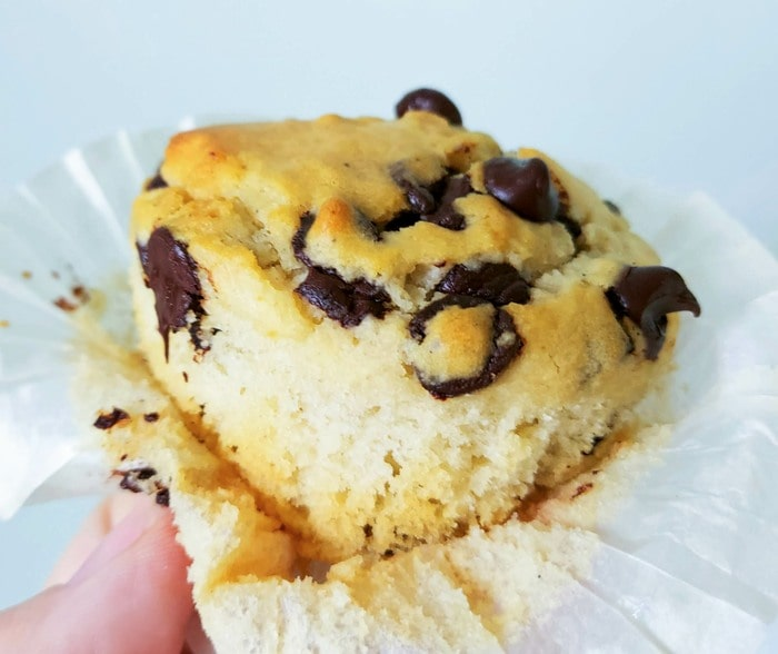 Muffin with the paper case peeled back, with melty chocolate chips
