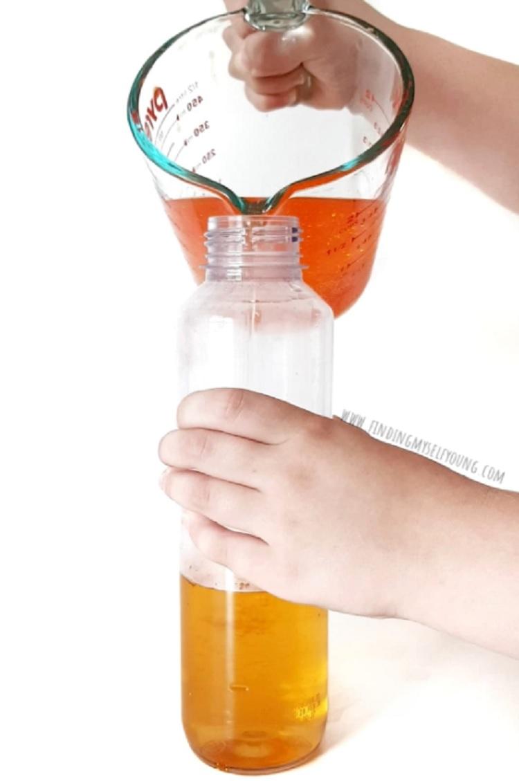 pouring mixture into sensory bottle