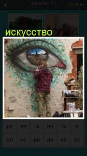 мужчина художник рисует на стене большой глаз 22 уровень 667 слов