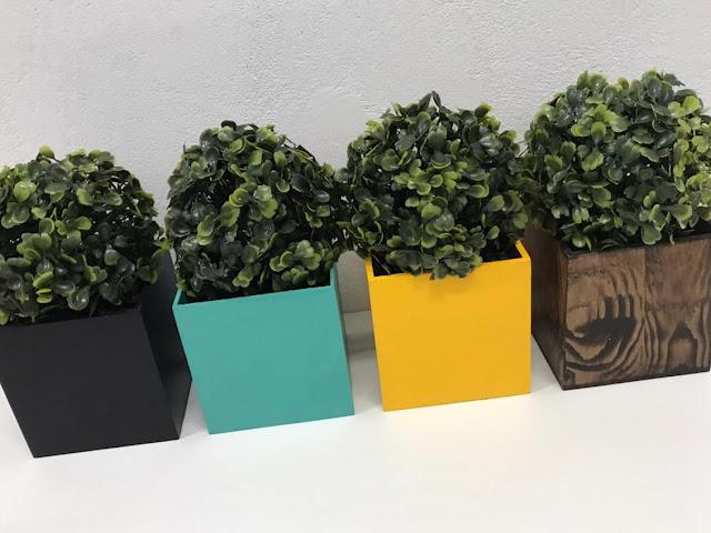 Quatro cachepots coloridos: preto, turquesa, amarelo e marrom com plantinhas permanentes do tipo buxinho.