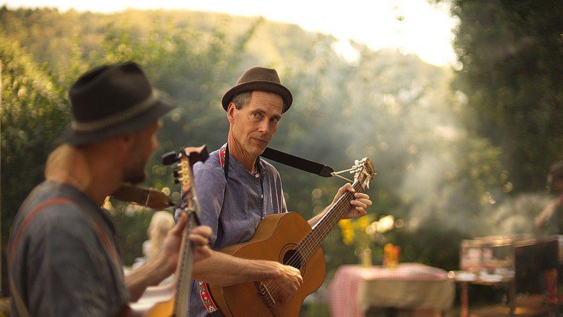 Мужчины играют на гитарах