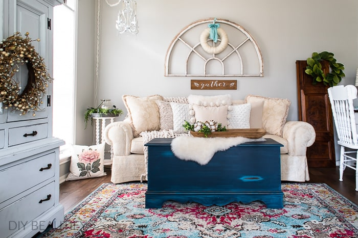 cozy cottage decor with patterned rug, neutral sofa, antique window and wool wreath
