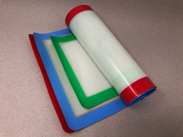 3 silcone baking mats with red, blue and green borders partially rolled up