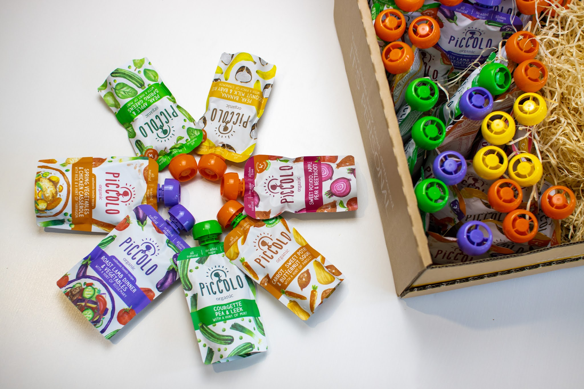 6 baby food pouches arranged in a flower shape next to a delivery box full of baby food from piccolo subscription service