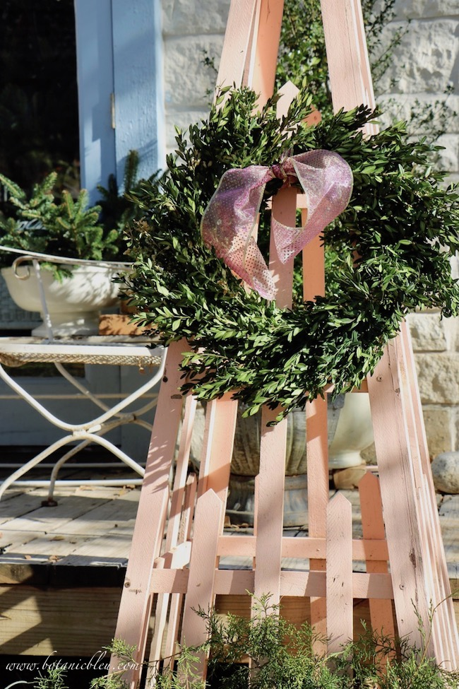 Christmas greenery on a peach colored trellis in the style of French Country tuteurs