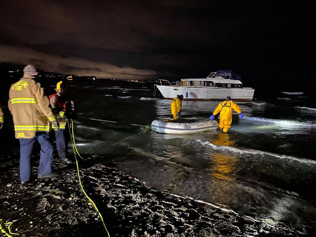 A pretty white cabin cruiser floats just offshore. Two people in yellow rainsuits and boots are knee deep in water, floating a small rubber boat between them. Two people in yellow rain jackets are on shore. The whole scene is lit with floodlights. Tiny waves are breaking on the beach.