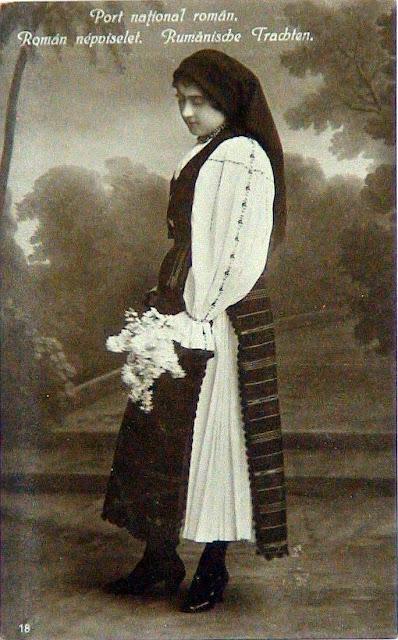 femeie cu buchet de flori in costum popular din Transilvania
