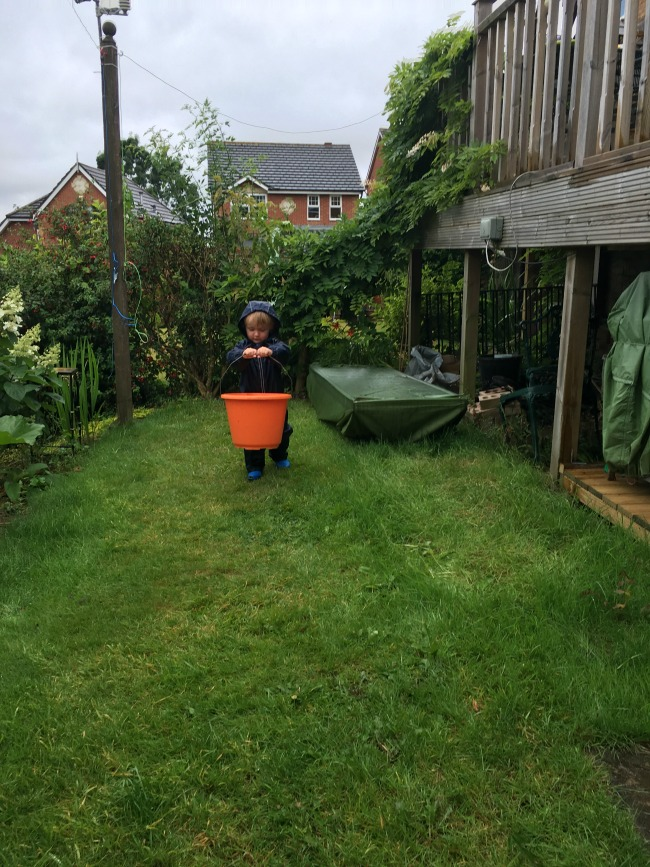 8-ways-to-entertain-a-toddler-in-a-typical-British-Summer-toddler-in-garden-with-bucket