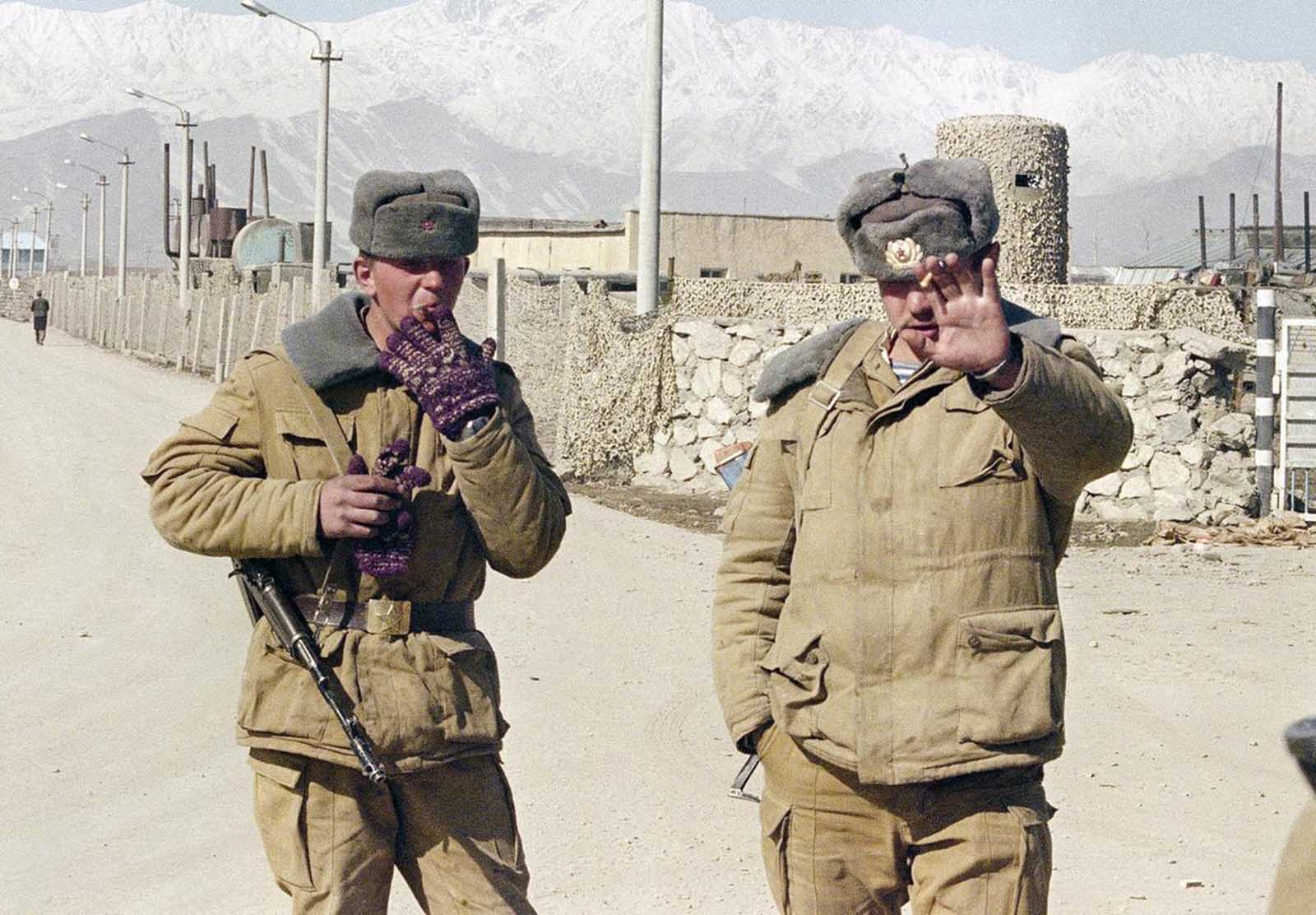 A Soviet soldier smokes a cigarette at a checkpoint of the Soviet military airport in Kabul on February 10, 1989 as the other one forbids pictures.