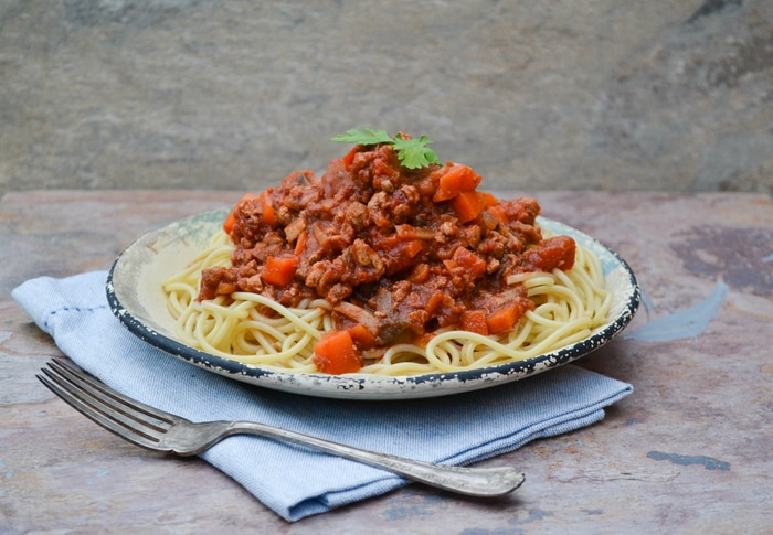 A plate full of spaghetti topped with veggie spaghetti bolognese sauce