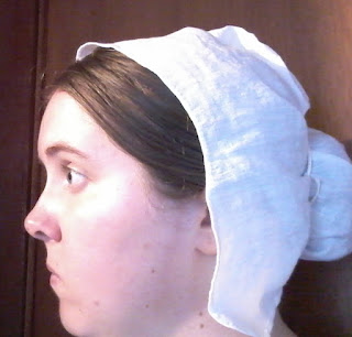 The author wearing a white coif over her hair; the back drawstrings tie around the coil of hair.