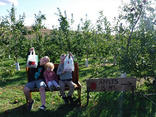 three children with blondish hair sit together on a wooden bench amidst apple trees while proudly holding bags of apples theyve picked.