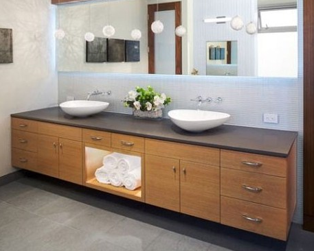 Vanity wood cabinets are combined with beautiful soft-colored tiles.