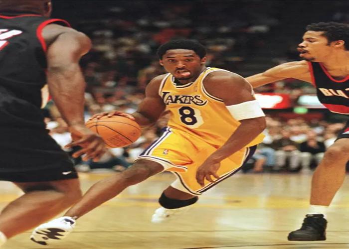 Pemain Los Angeles Lakers, Kobe Bryant membawa bola melewati pemain Portland Trailblazers Rasheed Wallace selama pertandingan playoff di Los Angeles pada 24 April 1998.