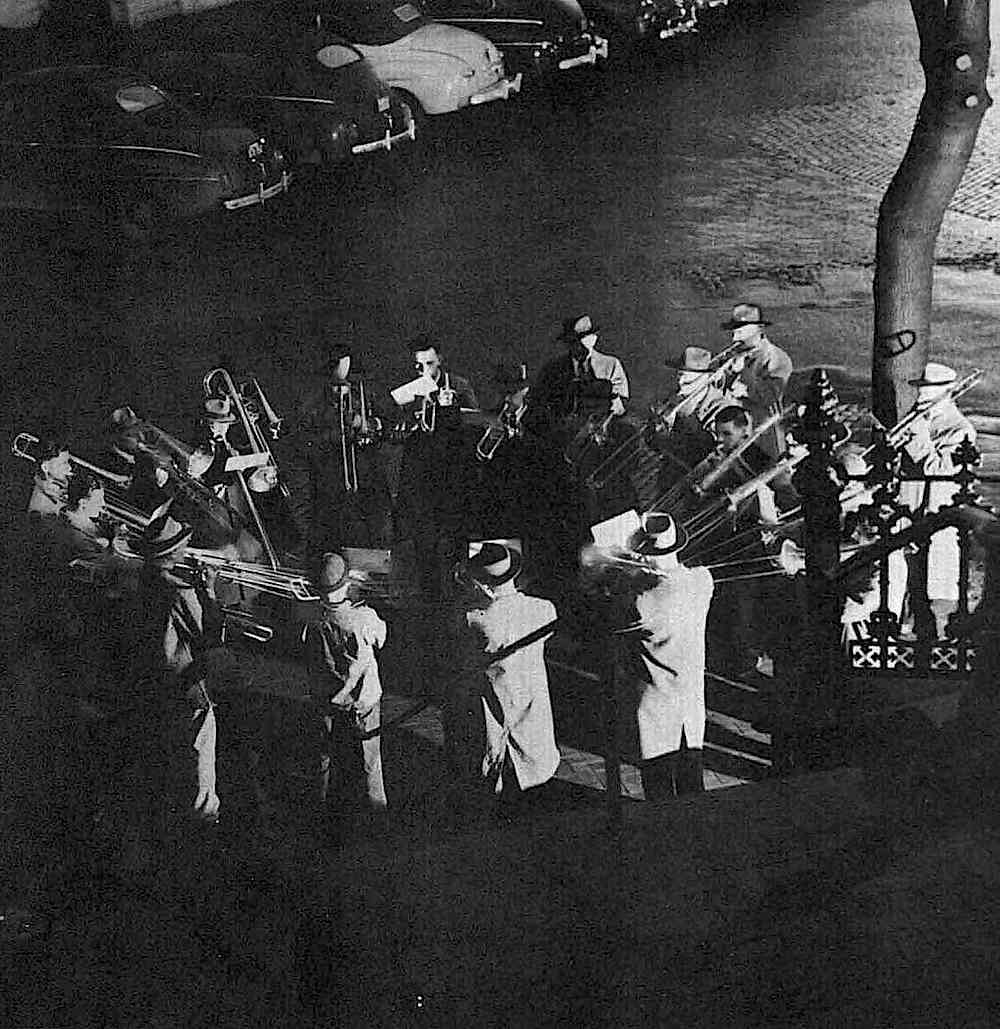 a 1957 photograph of a ring of trombone players at night