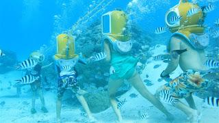 Groupe de personnes en scaphandre sous l'eau. Visite des récifs coralliens à Tahiti.