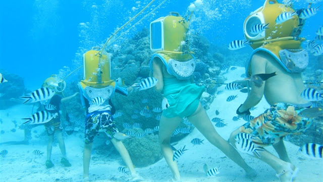 Groupe de personnes en scaphandre sous l'eau