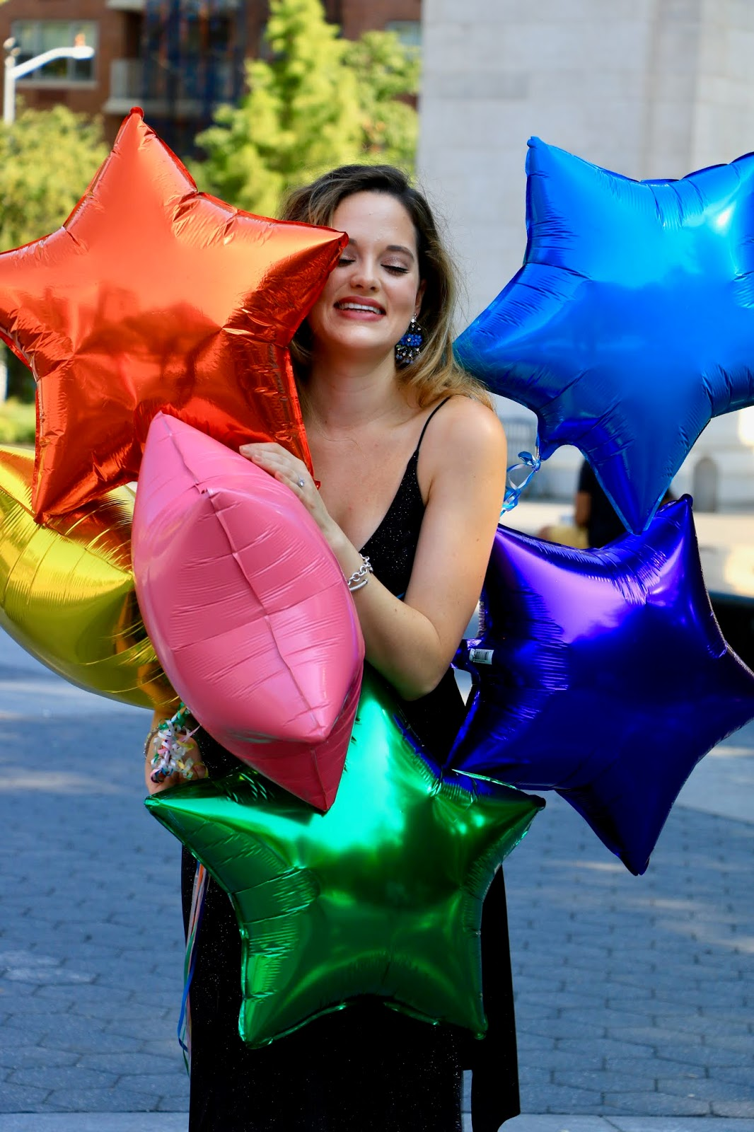 Nyc fashion blogger Kathleen Harper holding star-shaped balloons from the Upper Westside.