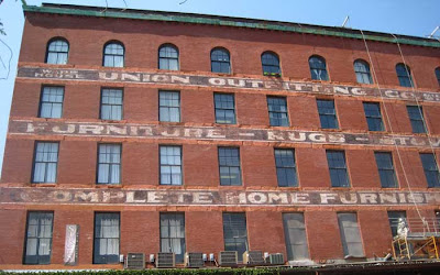 Brick warehouse with faded letters of a 19th century sign running between the windows of all the floors