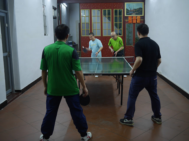 four men playing ping-pong