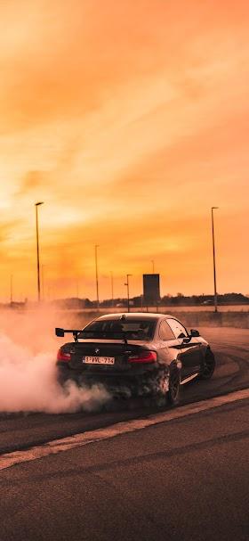 Black BMW drifting on road wallpaper
