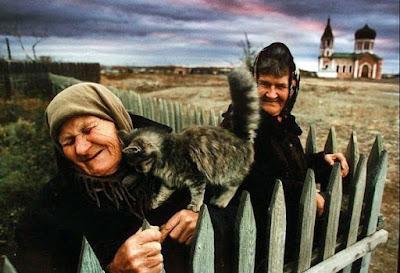 Alte Weiber am Gartenzaun mit Katze