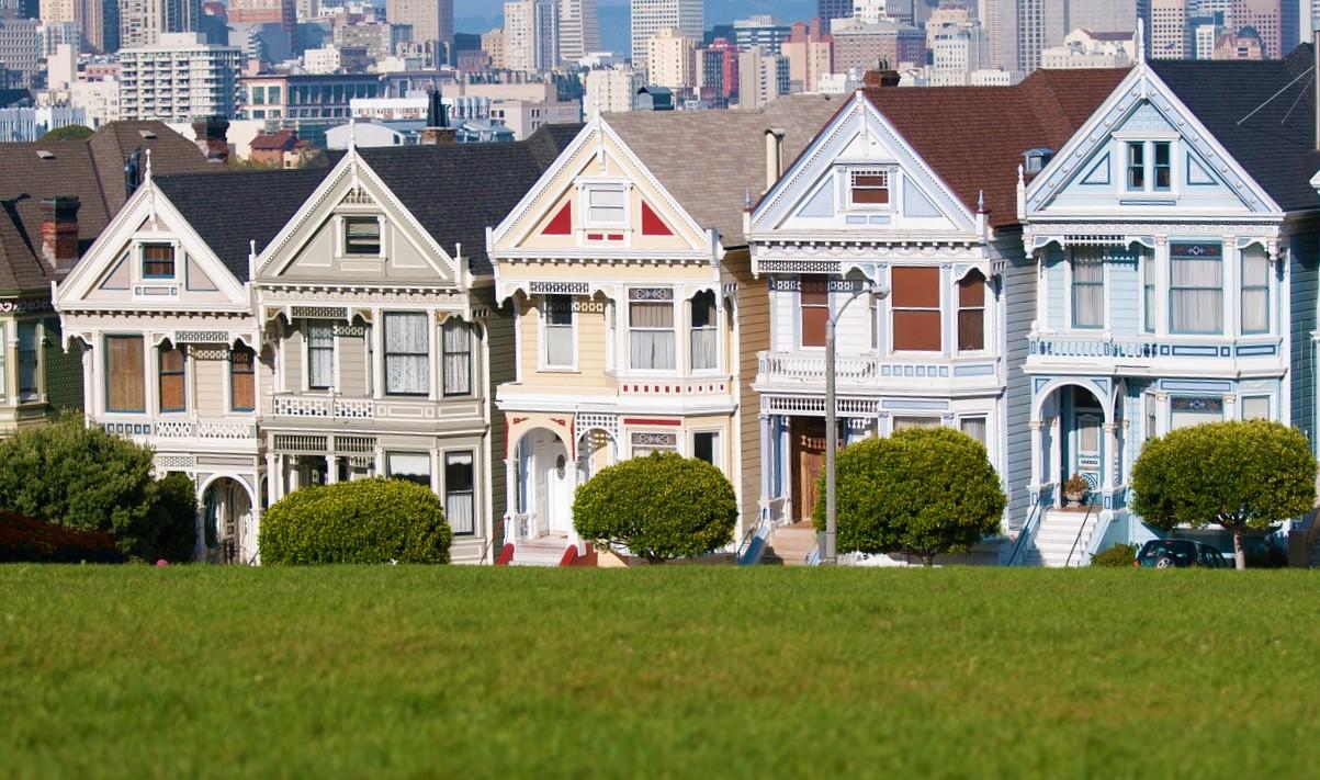 conjunto de casas vitorianas restauradas nas cores verde-musgo, creme e azul-bebê