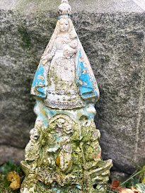 A weathered devotional statue of the Virgin Mary placed next to a gravestone in Greenwood Cemetery, Brooklyn.